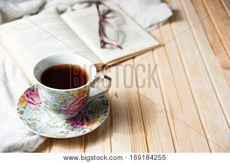 cup of coffee or tea on wooden table with open book and glasses, copyspace