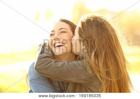 Two happy friends hugging and kissing in the street at sunset with a warm light
