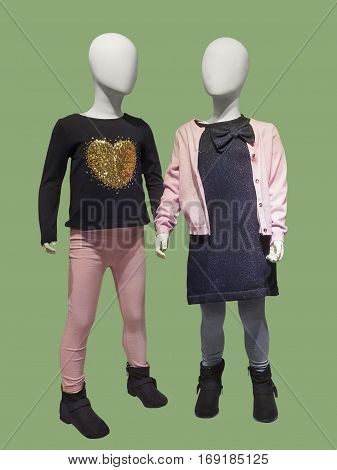 Two mannequins dressed in fashionable kids wear. Isolated on green background. No brand names or copyright objects.
