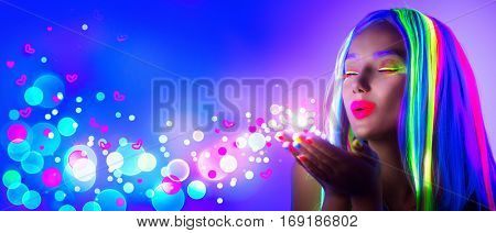 Valentine's Day girl on disco party. Fashion model woman in neon light, blowing Valentine neon hearts. Beautiful model girl, painted fluorescent make-up, Body Art design of female in UV. Night club