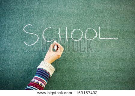 Handwritten message on a chalkboard at school: school. Hand in a winter pullover