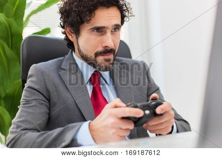Laze businessman playing videogames in his office