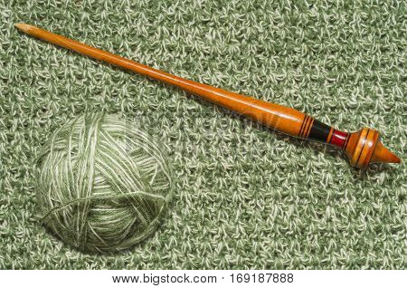 The ball of yarn on a background of knitted fabrics and old spindle.