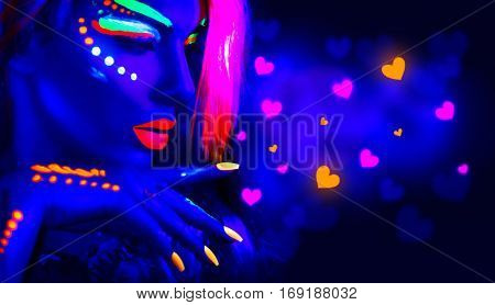 Valentine's Day girl on disco party. Fashion model woman in neon light, flying Valentine neon hearts. Beautiful model girl, painted fluorescent make-up, Body Art design of female in UV. Night club