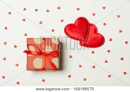 A gift on a wooden background with hearts. Surprise your loved one. The concept of the day of St. Valentine's weddings engagements Mother's Day birthday New Year Christmas holidays. Flat fly