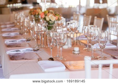 Table at wedding reception decorated with flowers candles and set with cutlery and crockery