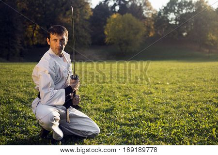 Ninja in white kimono with sword is outdoors in the park.