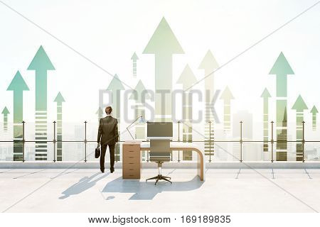 Back view of businessperson in abstract roof office with bright daylight and abstract upward arrows. Success concept