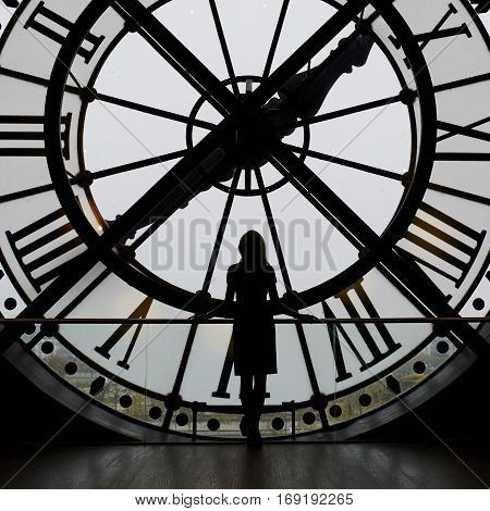 Woman Silhouette Standing In Front Of Large Clock