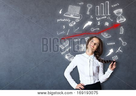Pretty young woman daydreaming on concrete wall background with business icons and growing red arrow. Success concept