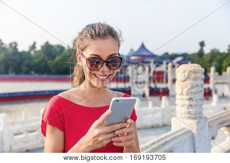 Asian tourist using phone app to find directions and guide during travel in Beijing, China. Happy Chinese woman texting on mobile sms smartphone.