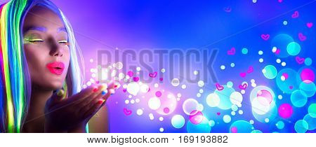 Valentine's Day girl on disco party. Fashion model woman in neon light, blowing Valentine neon hearts. Beautiful model girl, painted fluorescent make-up, Body Art design of female in UV. Night club.