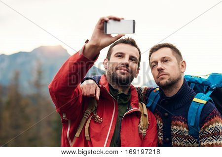 Two young men in hiking gear standing outside taking a selfie with mountains behind them while out trekking in the wilderness