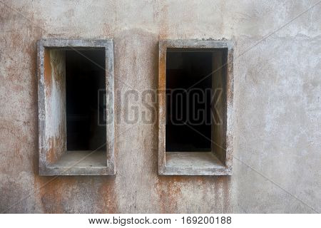 two empty window openings on an old stone wall and a blank space for the text