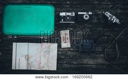 Vintage hipster suitcase packing before travel with old suitcase camera and accessories on a wooden table top view