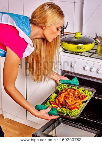 Woman in kitchen is cooking roast meat food in oven. Chicken is oven- tray with lettuce leaf. Housewife wearing apron in white home interior preparing barbecue dinner for friends.