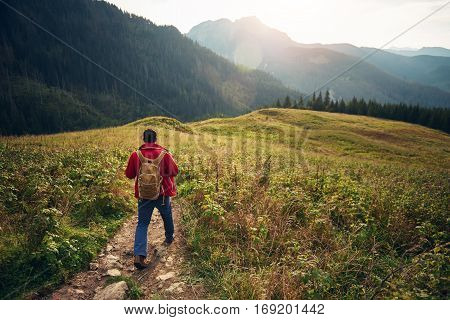 Rearview of a young man wearing a backpack and carrying trekking poles walking down a trail in the mountains