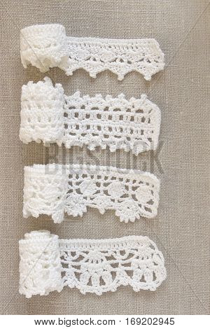 Handmade crocheted cotton organic lace ribbons on linen background. White original organic crochet frame Knitted pattern backdrop with handicraft work Mori Girl lace style. Needlework creative craft