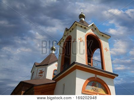 Christian church architecture in white with gold domes closeup with paintings in black and oranges