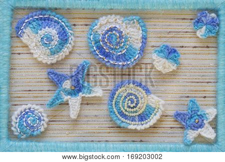 Marine background with cotton lace crochet craft elements: stars shells flowers and frame made of soft acrylic like wool yarn. Crocheted creative small doilies. Decorative needlework marine design