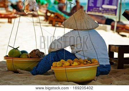 PHU QUOC, VIETNAM - APRIL 26, 2014: Vietnamese fruits saleswoman with traditional headdress, which protects from the sun, resting on in shadow of beach umbrella Long beach on Phu Quoc island, Vietnam