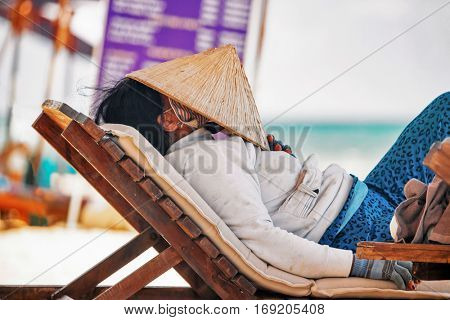 PHU QUOC, VIETNAM - APRIL 26, 2014: Vietnamese fruits saleswoman with traditional headdress, which protects from the sun, resting on a lounger on Long beach on Phu Quoc island, Vietnam
