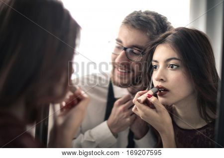 Brown-haired couple getting ready to go out in front of the same mirror