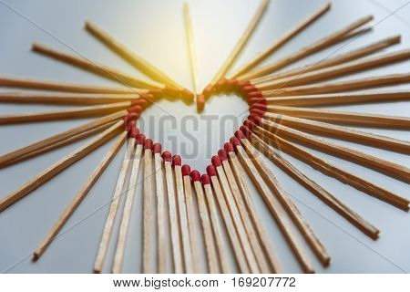 closeup of matchsticks arranged to form a heart shape with depth of field