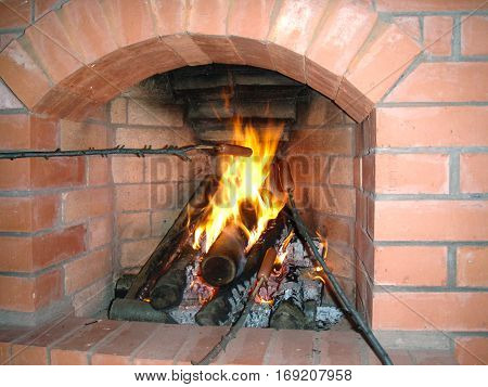 cozy fireplace of brick in the house preparing sausage on a branch