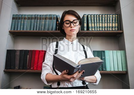 View from below of Authoress in glasses and white shirt reading book with bookshelf on background