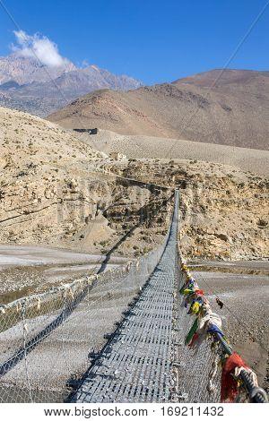 Suspension bridge with buddhist prayer flags on the Annapurna circuit trek in Nepal