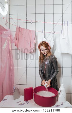 Charming young woman listening to music and washing clothes by hands in bathroom