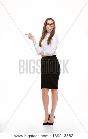 Full length portrait of a smiling excited businesswoman in eyeglasses pointing finger away over white background and looking at camera