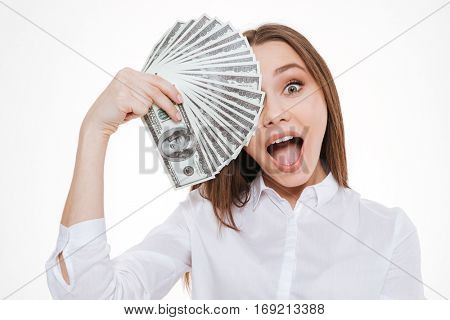 Happy young woman in formalwear holding paper currency infront of her face while standing isolated on white