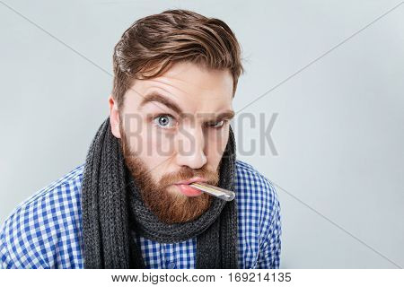 Amusing bearded young man in scarf holding thermometer in his mouth