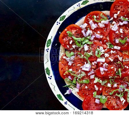A plate of sliced tomatoes with shallots and basil
