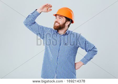 Happy bearded young man in helmet standing and looking far away