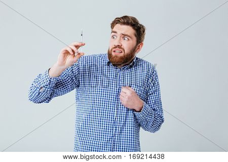 Portrait of terrified afraid young man with syringe