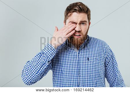 Upset bearded young man standing and rubbing his eye