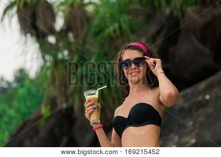 Female model girl in sunglasses posing with fresh cocktail on the Beach