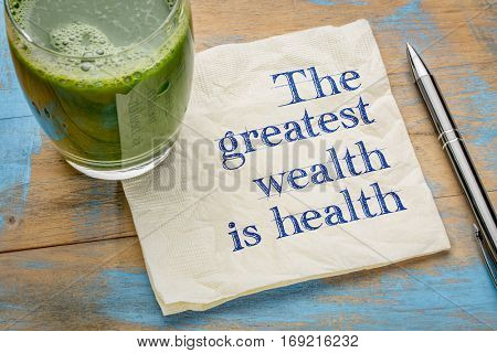 The greatest wealth is health advice or reminder - handwriting on a napkin with a glass of fresh, green, vegetable juice