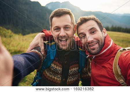 Two smiling young men in hiking gear standing outside taking a selfie with mountains behind them while out trekking in the wilderness
