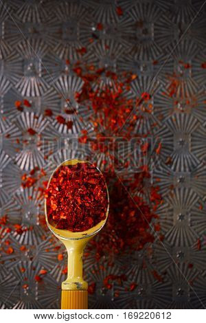 red hot chillies pepper flakes in vintage ice-cram spoon on textured metal background