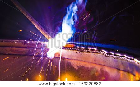 Shielded metal arc welding and welding flame at spark point.