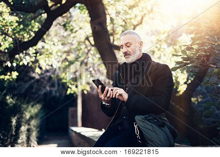 Portrait of successful middle age businessman using modern smartphone while spending time in city park at sunny day.Horizontal, blurred background