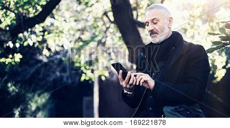 Portrait of successful middle age businessman using modern smartphone while spending time in city park at sunny day.Horizontal wide, blurred background