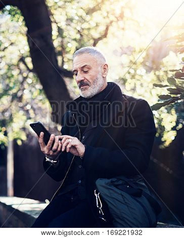 Portrait of successful middle age businessman using modern smartphone while spending time in city park at sunny day.Vertical, blurred background
