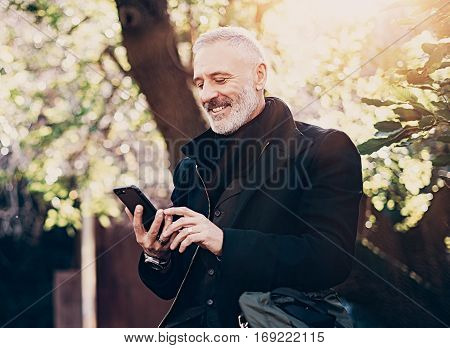Portrait of smiling and happy middle age businessman using modern smartphone while spending time in city park at sunny day.Horizontal, blurred background