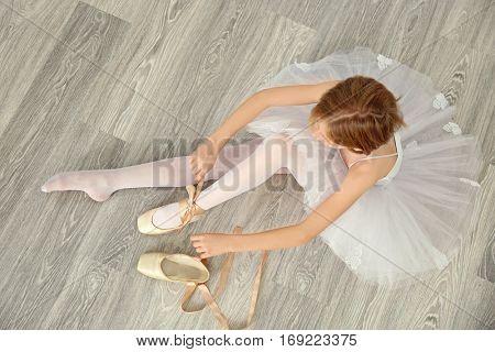Ballerina tying ballet shoes on wooden floor