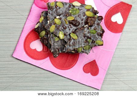 Top down view of a stack of dark chocolate bark with pine nuts and cranberries with copy space